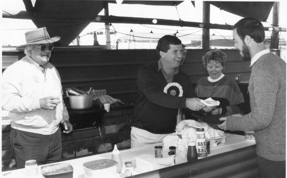 New CLP President Shane Stone serves a steak sandwich to Alex Nelson at the CLP's original stand at the Alice Springs Show at Blatherskite Park in 1988. The Show was held on July 1 and 2 that year, coinciding with the tenth anniversary of NT Self-Government. One decade later Chief Minister Shane Stone presided over the failure of the referendum for statehood for the NT. From left: Dave Bottrall, CLP President Shane Stone (obscuring Dave Tuzewski), June Tuzewski, and Alex Nelson. Photo by Ruth Andrews.